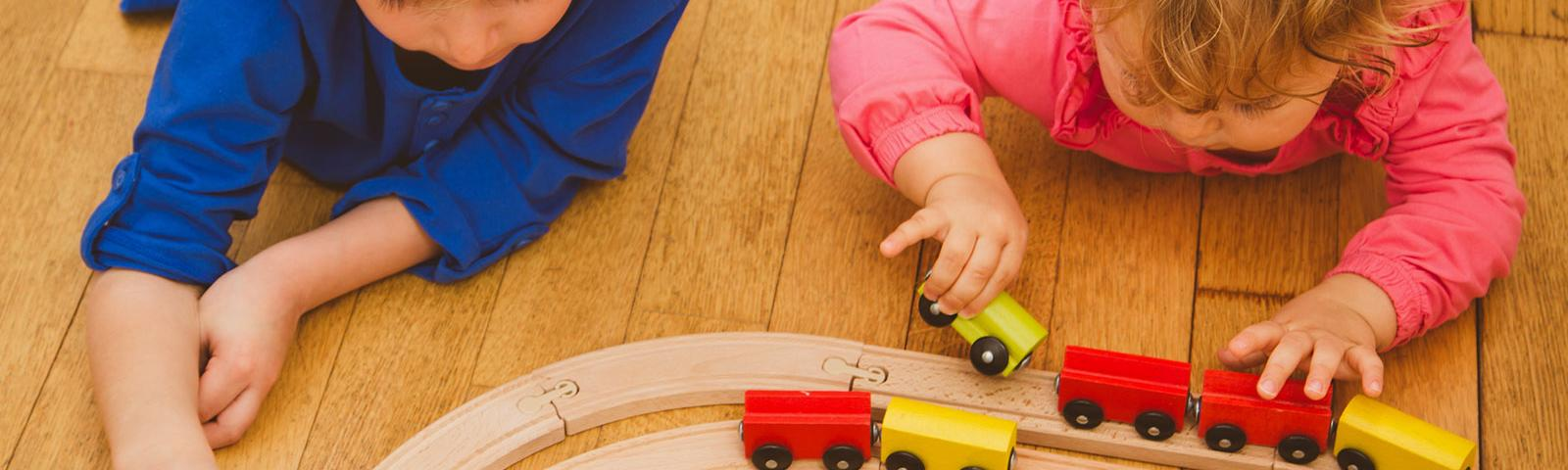 two preschool age children lying on wood floor, playing with toy trains