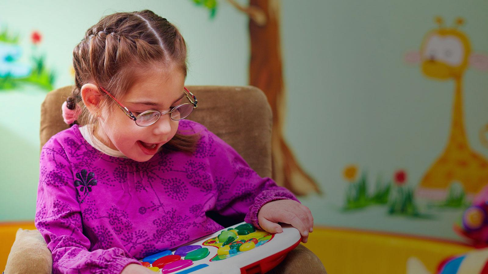 happy girl in wheelchair playing with developing toy in daycare center