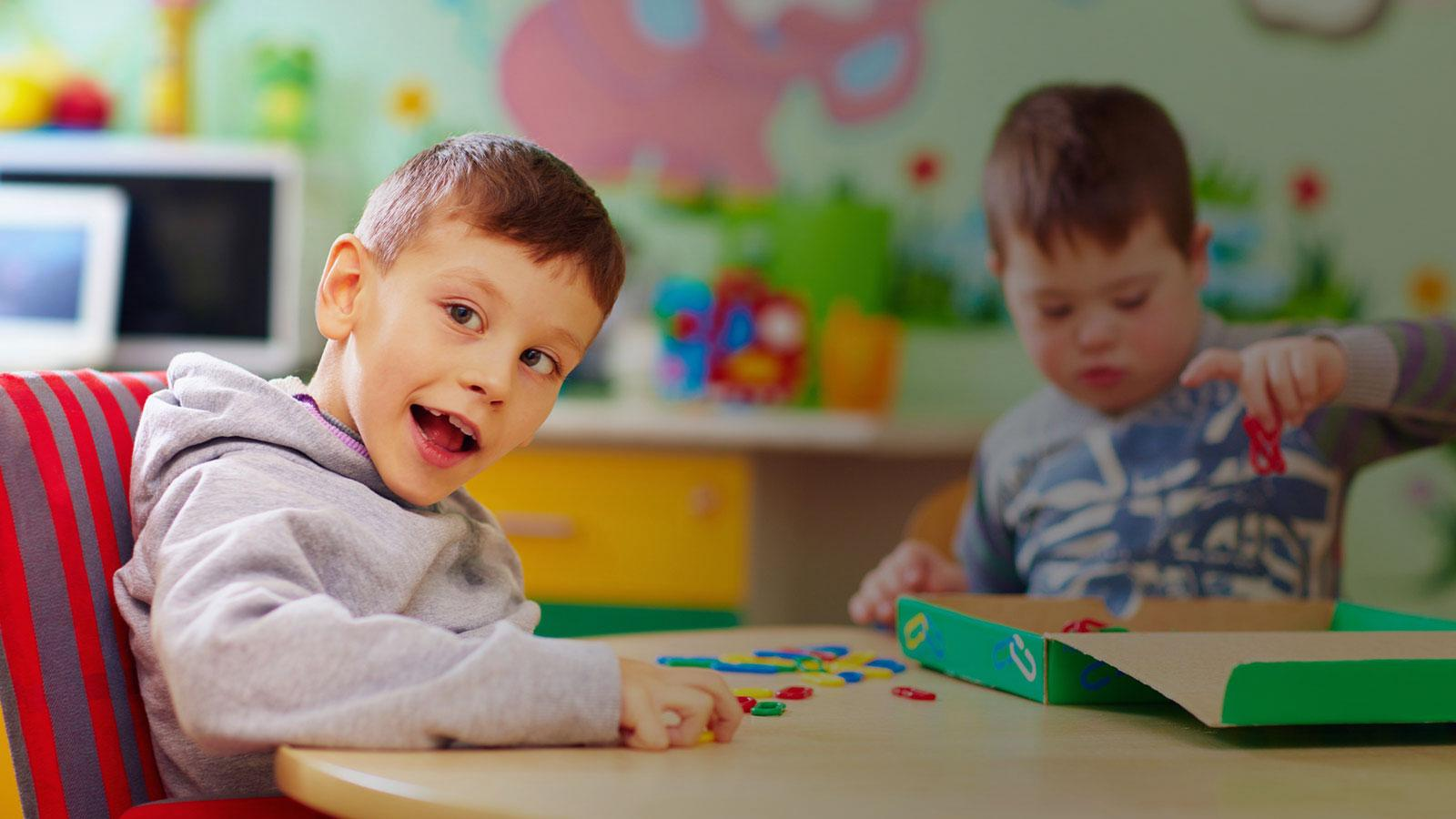 2 boys with special needs playing with toys while sitting at desk in daycare
