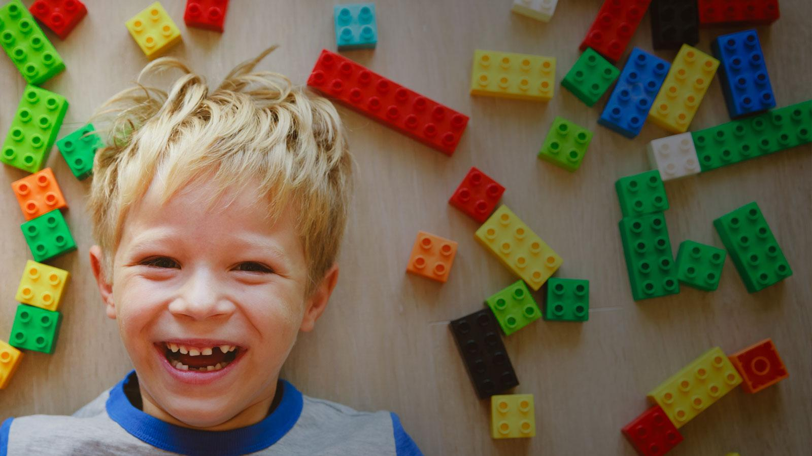 happy little boy playing with plastic blocks