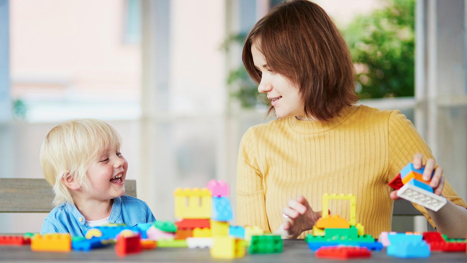 preschool teacher and young child playing with blocks