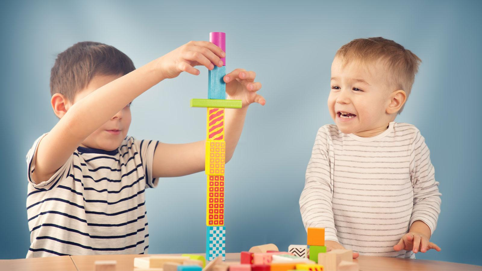 two preschool boys having fun stacking blocks